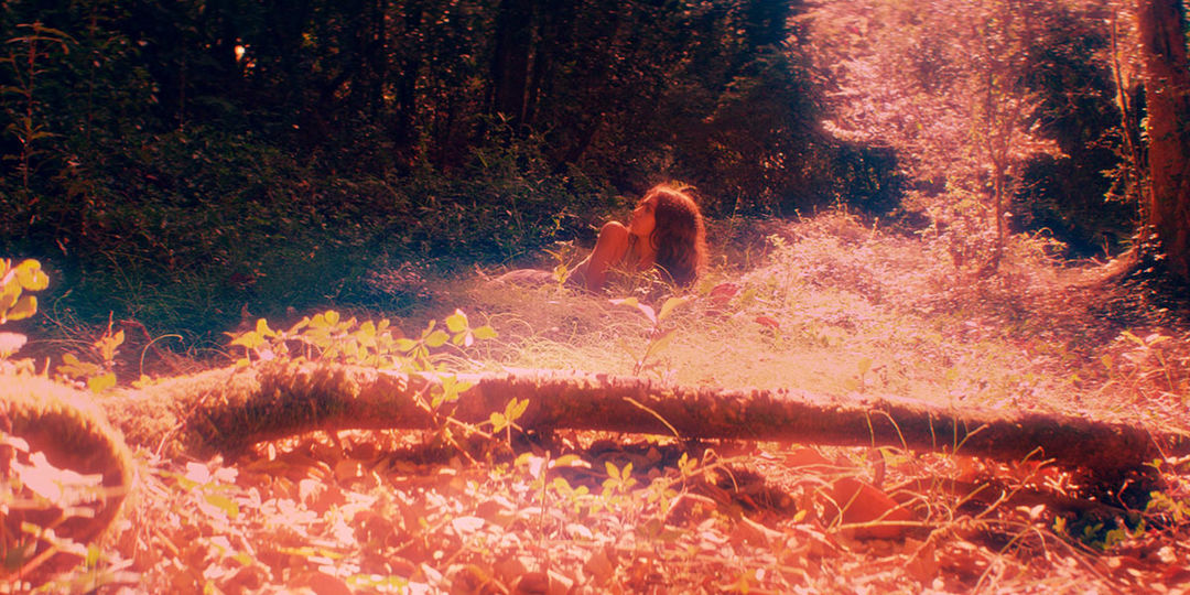 IMAGE: Still - Tamara in red light lying in grass
